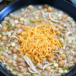 Black bowl filled with white chicken chili and topped with shredded cheese.