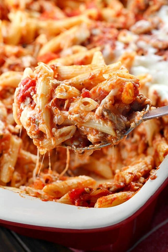 A scoop of Skinny Cheesy Pasta Bake on a silver spoon from a casserole dish.