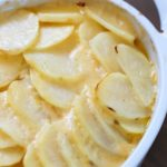 Cheesy Potatoes au Gratin made with a homemade cheese sauce drizzled over thinly sliced potatoes and a layer of onions nestled in the middle. A great Thanksgiving recipe! Plus a full blog hop Thanksgiving menu to help plan your turkey day meal!