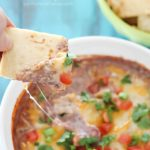 Pita chip is dipped into a cheesy Healthy Black Bean Dip + 43 Healthy Snack Ideas!