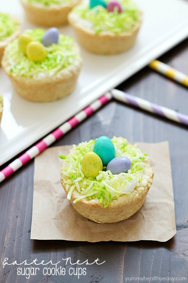 Need a fun treat to make for an Easter get together? Make these darling Easter Nest Sugar Cookie Cups! Sugar cookie dough cooked in a muffin tin, filled with vanilla frosting, topped with green tinted coconut and M&M eggs to look like a little bird's nest. So cute and great for spring! #truvia