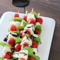 Summer afternoons call for these fun Caprese Skewers! Cherry tomatoes, fresh basil and cubes of mozzarella cheese threaded on skewers and drizzled with an easy balsamic reduction. Delicious!