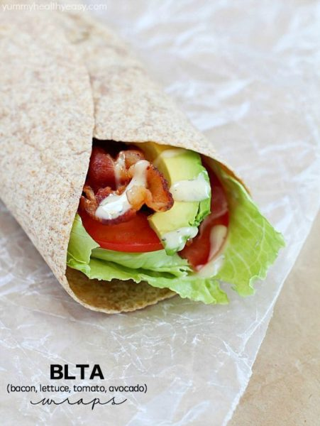 Bacon, Lettuce, Tomato & Avocado wrap on some parchment paper.