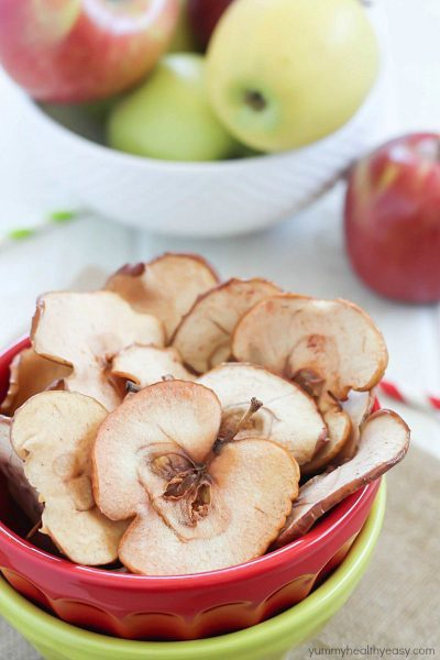 Homemade Apple Chips in a red and green bowl with fresh apples in the background.
