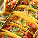 Ground Turkey Tacos that are oven-baked with layers of deliciousness inside! Refried beans, ground turkey taco meat, (no taco seasoning mix!) tomato, cilantro, green onions and cheese all baked in taco shells. Perfect for Taco Tuesday or for game day!