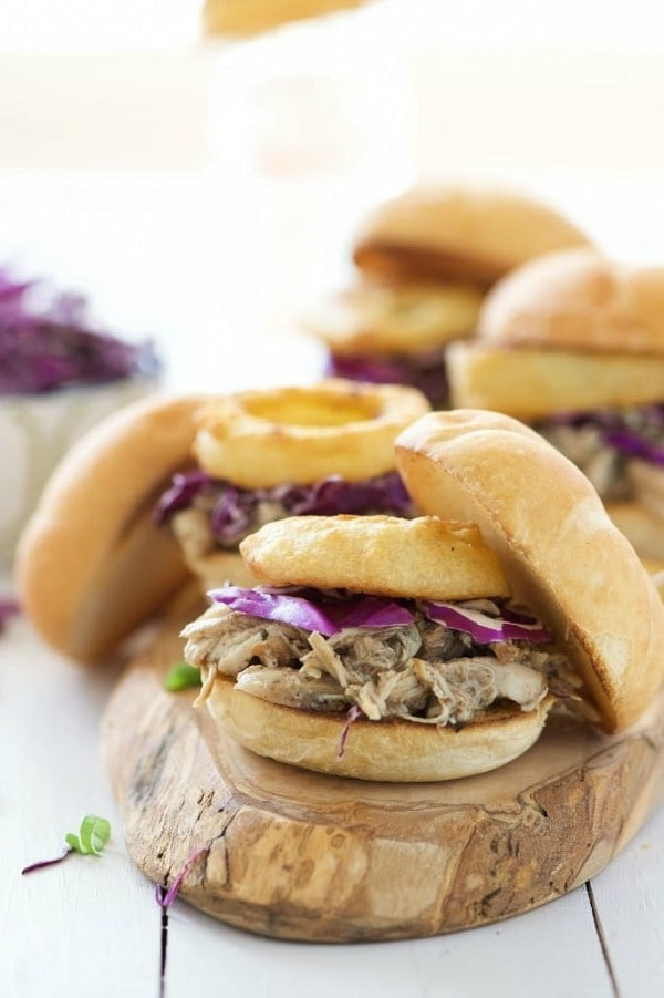 Brown Sugar Pulled Chicken Sandwiches have the most tender, slightly sweet chicken! The slow cooker makes dinner a breeze for these sliders that are topped with a tangy homemade honey mustard sauce and crispy onion rings!