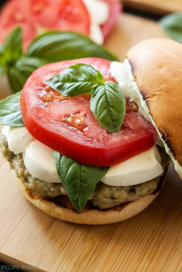 Juicy chicken burgers gone caprese style thanks to pesto, fresh basil, and thick slices of tomato and fresh mozzarella. These are a must make this summer!