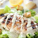 Grilled Chicken Caesar Salad for a yummy summertime lunch or dinner! With a simple yogurt marinade recipe, this grilled chicken is tender and delicious. Served over romaine lettuce, homemade croutons, shaved parmesan and caesar dressing - YUM!!