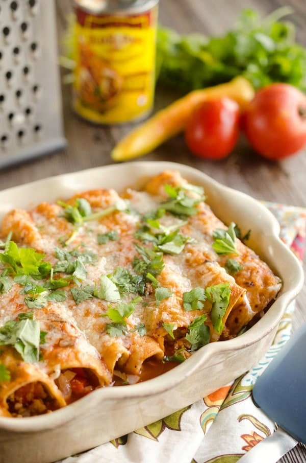 30 Minute Light Chicken Enchiladas are full of crumbled chicken & vegetables and a spicy enchilada sauce for an easy and healthy weeknight dinner!