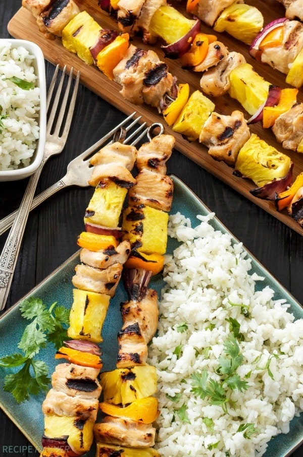 Hawaiian chicken skewers grilled with fresh pineapple, orange bell peppers, and red onions are an easy summer dinner! Serve the skewers with cilantro coconut rice as a delicious side dish!