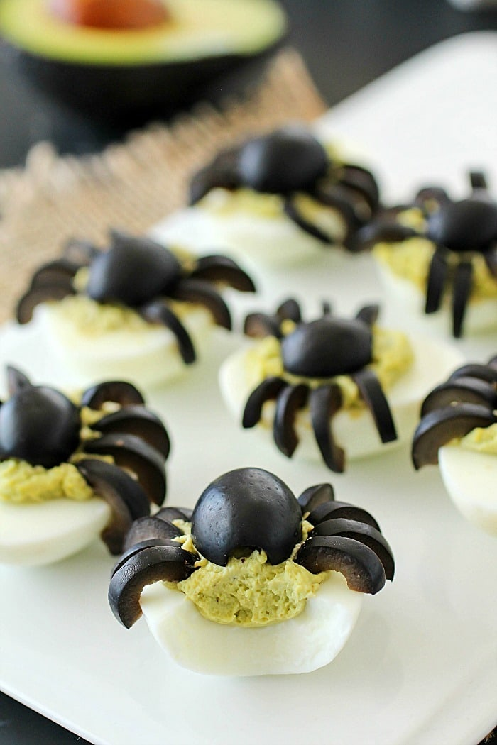 Celebrate Halloween with Spooky Spider Avocado Deviled Eggs! Your party guests will love these creepy crawly olive spiders on top of ghoulishly green avocado deviled eggs!