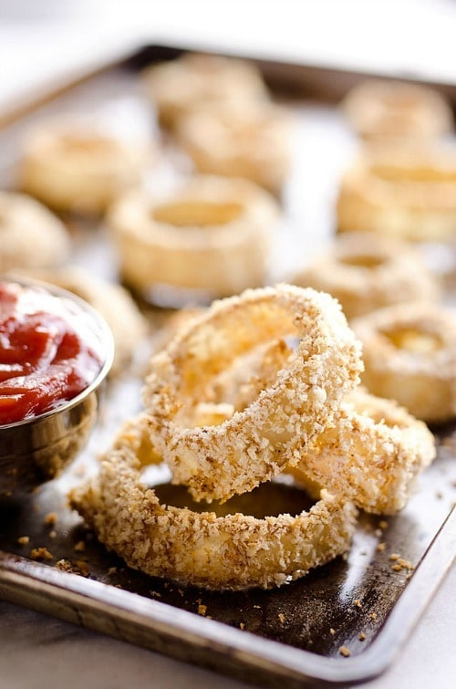 Baked Southwest Onion Rings are a lightened up version of a classic appetizer! Onions are coated in whole wheat flour, eggs, Panko bread crumbs and a mix of southwest spices and baked instead of fried for a healthy side dish.