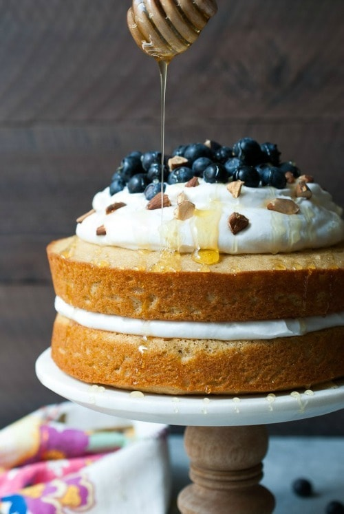This Lemon Blueberry Olive Oil Cake uses white whole wheat flour, greek yogurt, olive oil, and it's topped with an amazing coconut whipped cream, fresh berries, chopped almonds, and a drizzle of honey. What's not to love?
