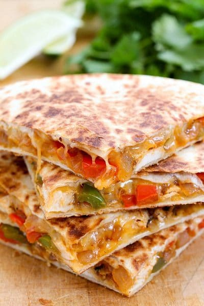 The Best Ever Cheesy Chicken Fajita Quesadilla on a cutting board.
