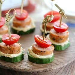 Low Carb Sausage Cucumber Bites skewered with toothpicks on top of a cutting board + 43 Healthy Snack Ideas
