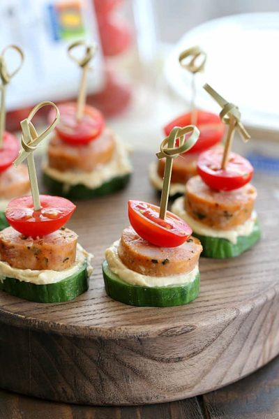 Low Carb Sausage Cucumber Bites skewered with toothpicks on top of a cutting board.