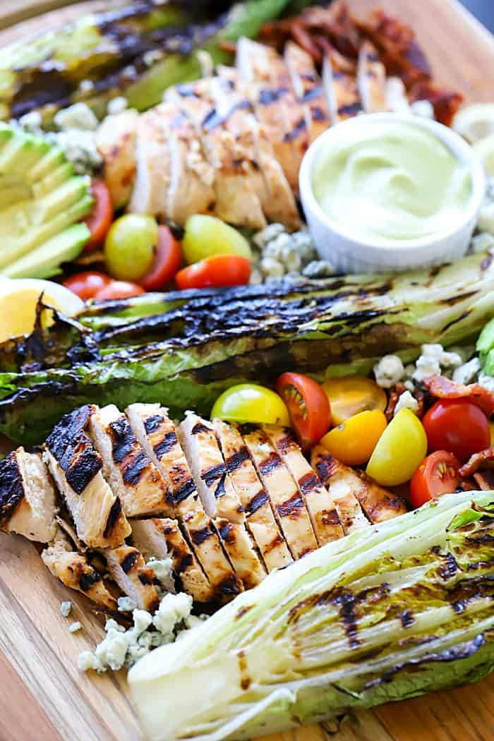Delicious view of a platter of Cobb salad ingredients: marinated and grilled chicken, grilled romaine, cherry tomatoes, avocado, blue cheese and bacon.
