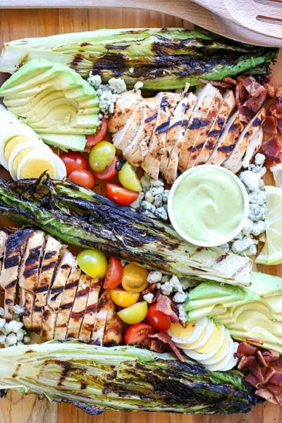 Deconstructed Cobb Salad on platter with marinated and grilled chicken, grilled romaine and other Cobb salad ingredients.