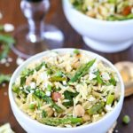 Top view of a beautiful Spring Orzo Salad filled with orzo, asparagus, toasted almonds, arugula, feta cheese and peas with a vinaigrette.