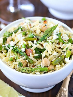 Beautiful Spring Orzo Salad filled with orzo, asparagus, toasted almonds, arugula, feta cheese and peas with a vinaigrette.