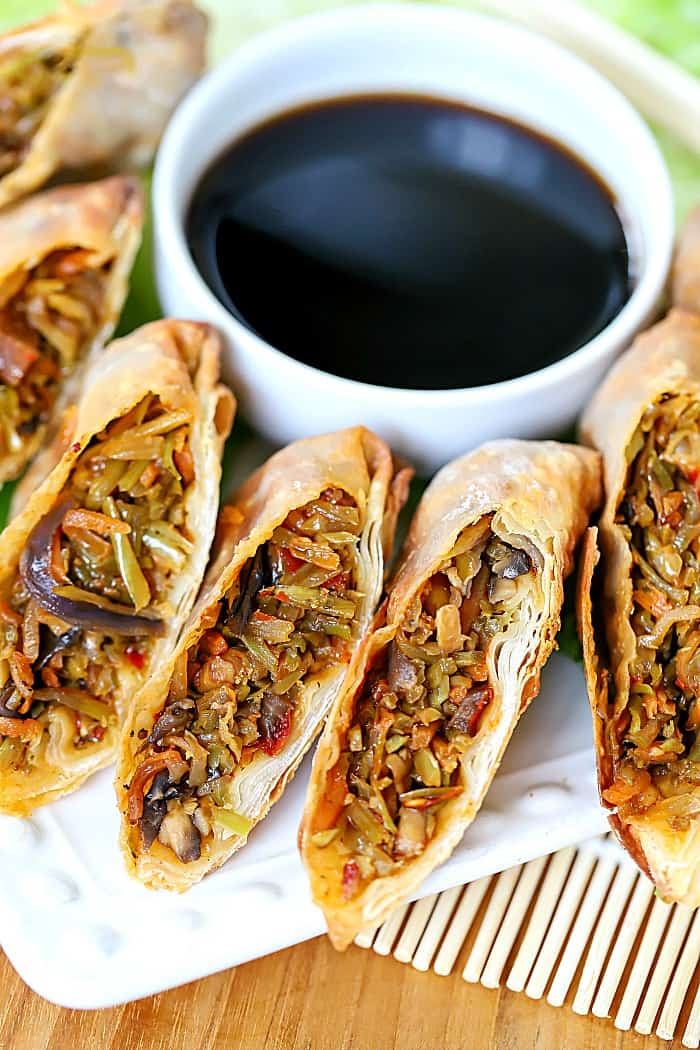 White plate with egg rolls sliced in half, surrounding a bowl of soy sauce.