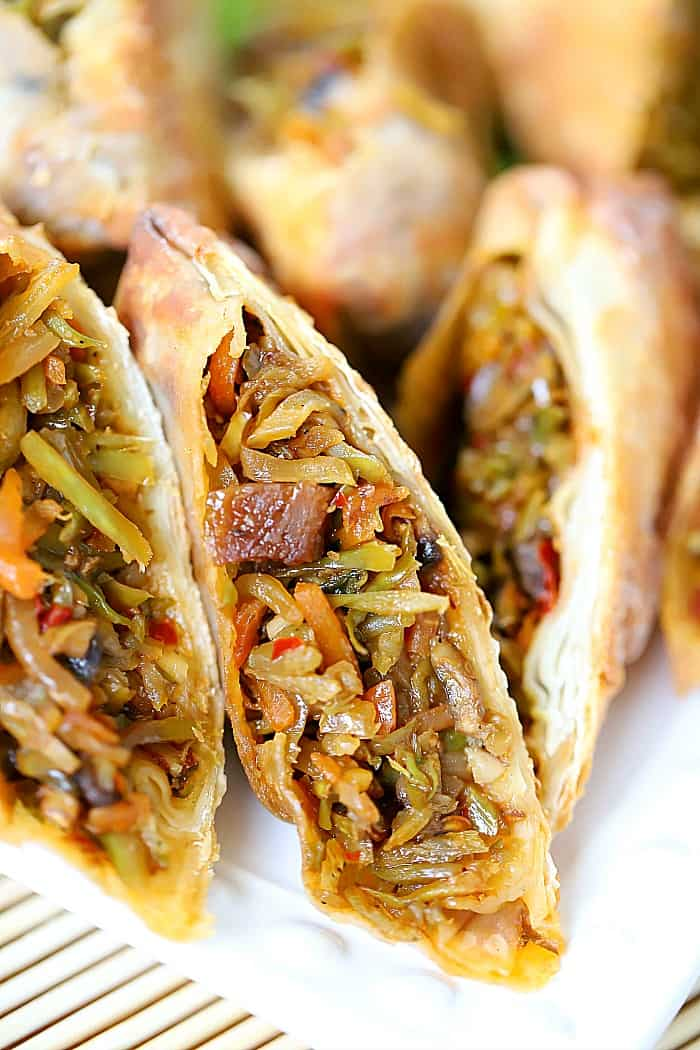 Close up view of the inside of a sliced in half egg roll showing cooked vegetables.