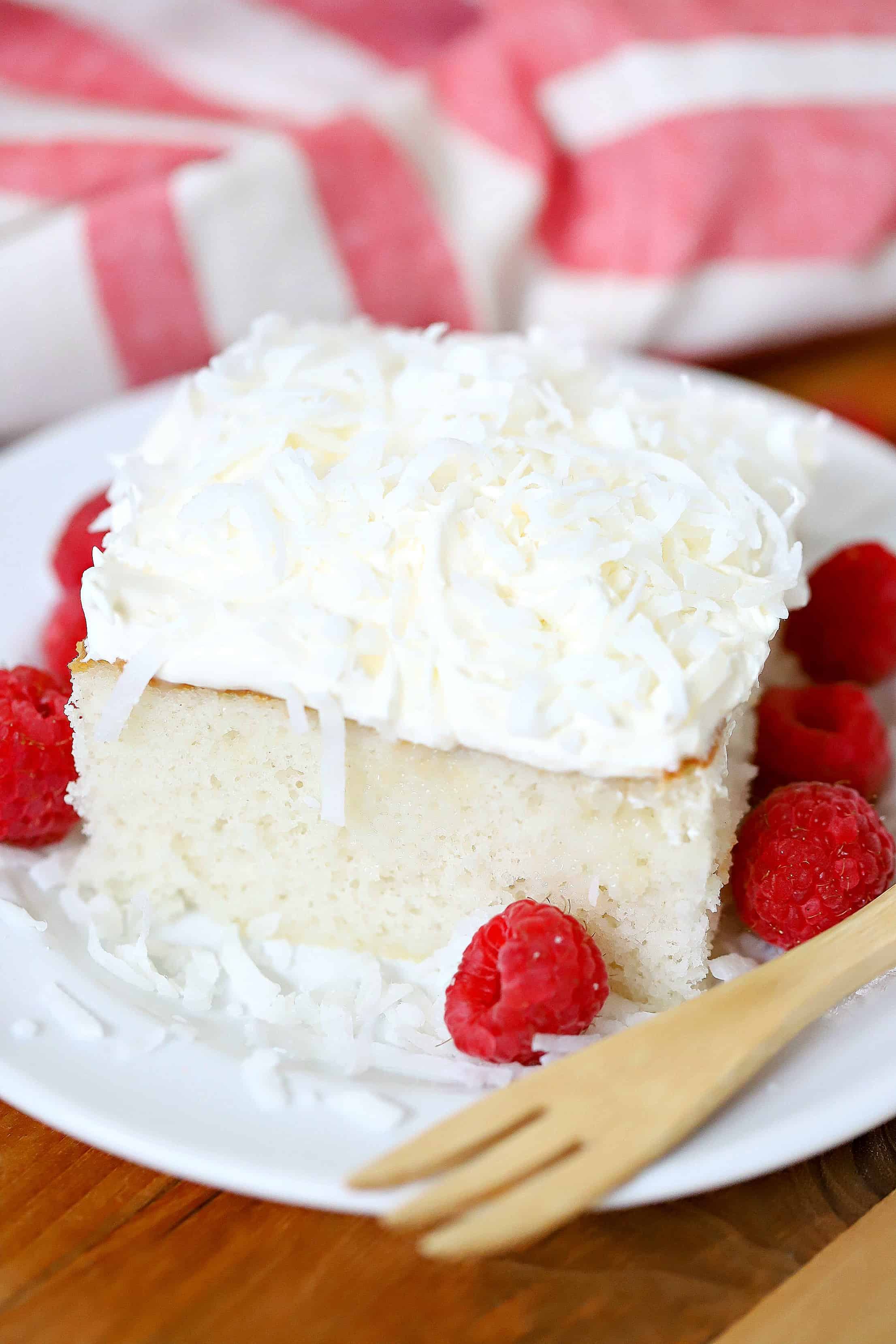 Piece of cake on a white plate with a side of raspberries and a fork.