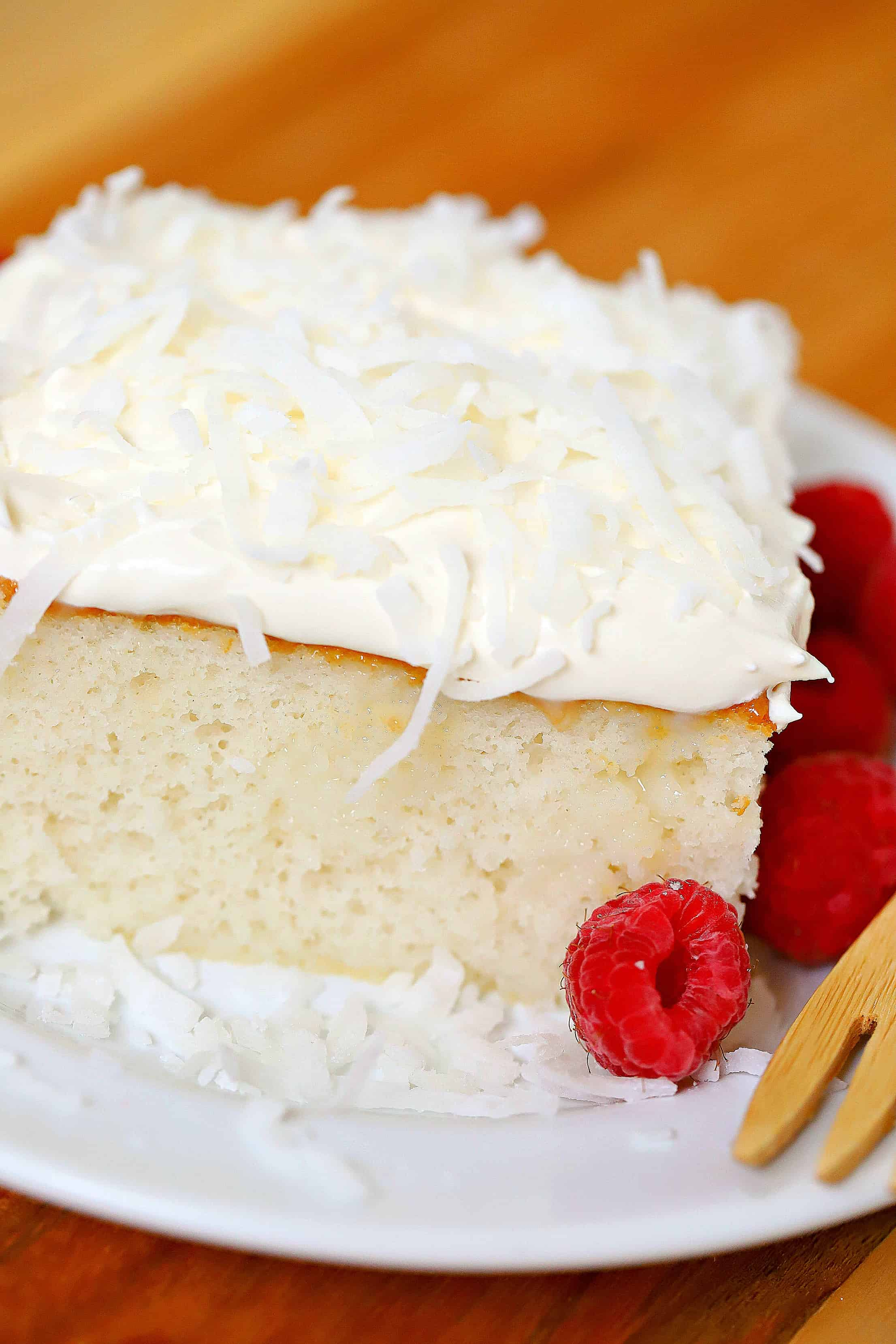 Coconut Cream Cake topped with whipped cream and coconut and a side of raspberries.