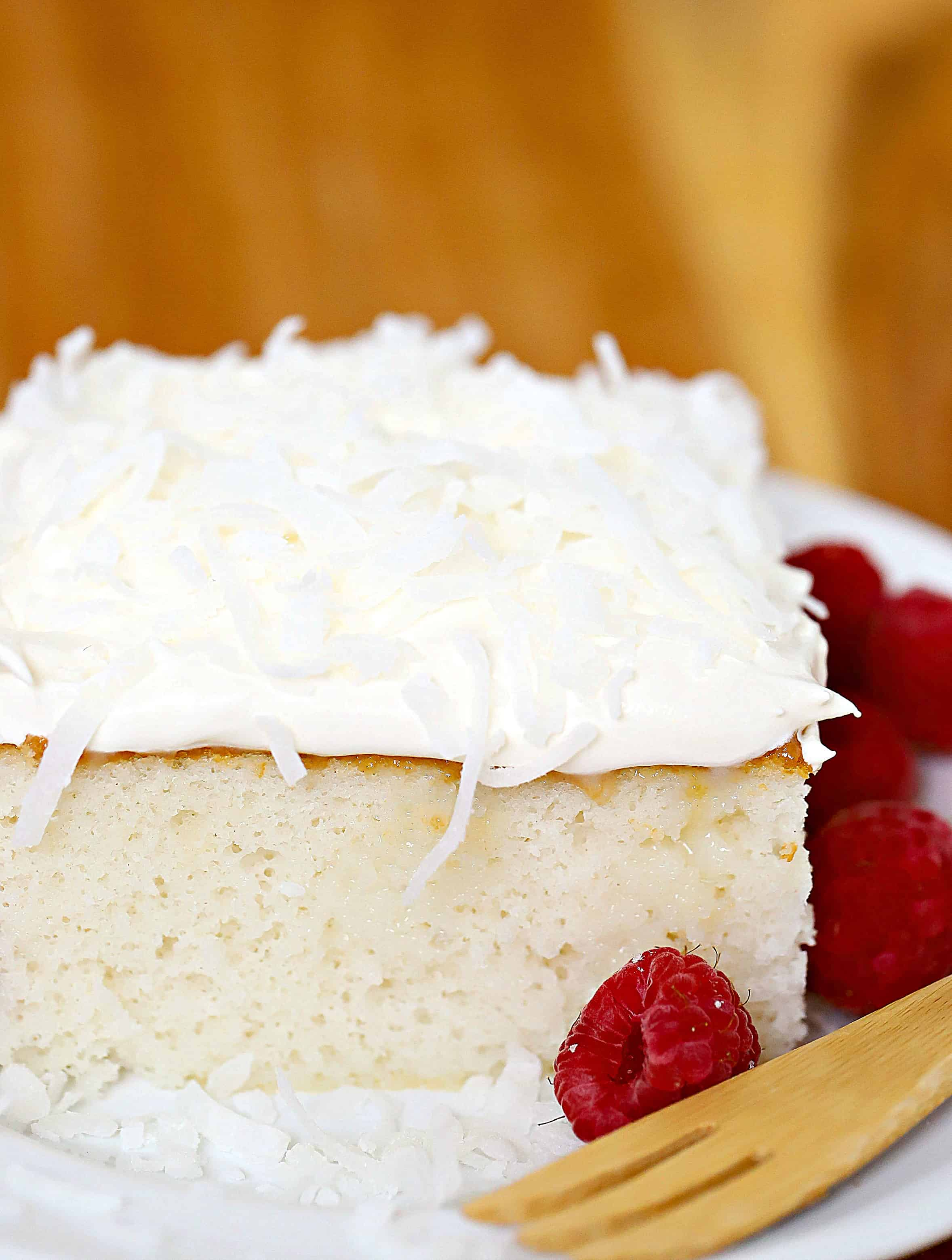 Close up of a square slice of cake topped with whipped cream and coconut and a side of raspberries.