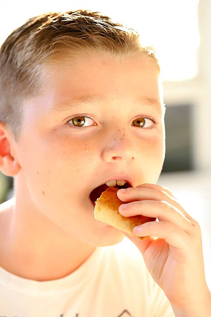 A cute boy eating a beef empanada