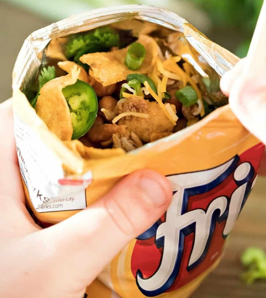 Frito bag filled with ground meat and beans with taco toppings and a fork.