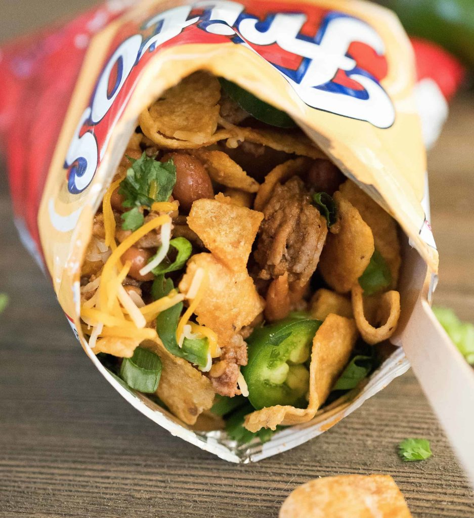 Close up of a Frito snack size bag filled with taco mixture and toppings. Yum!