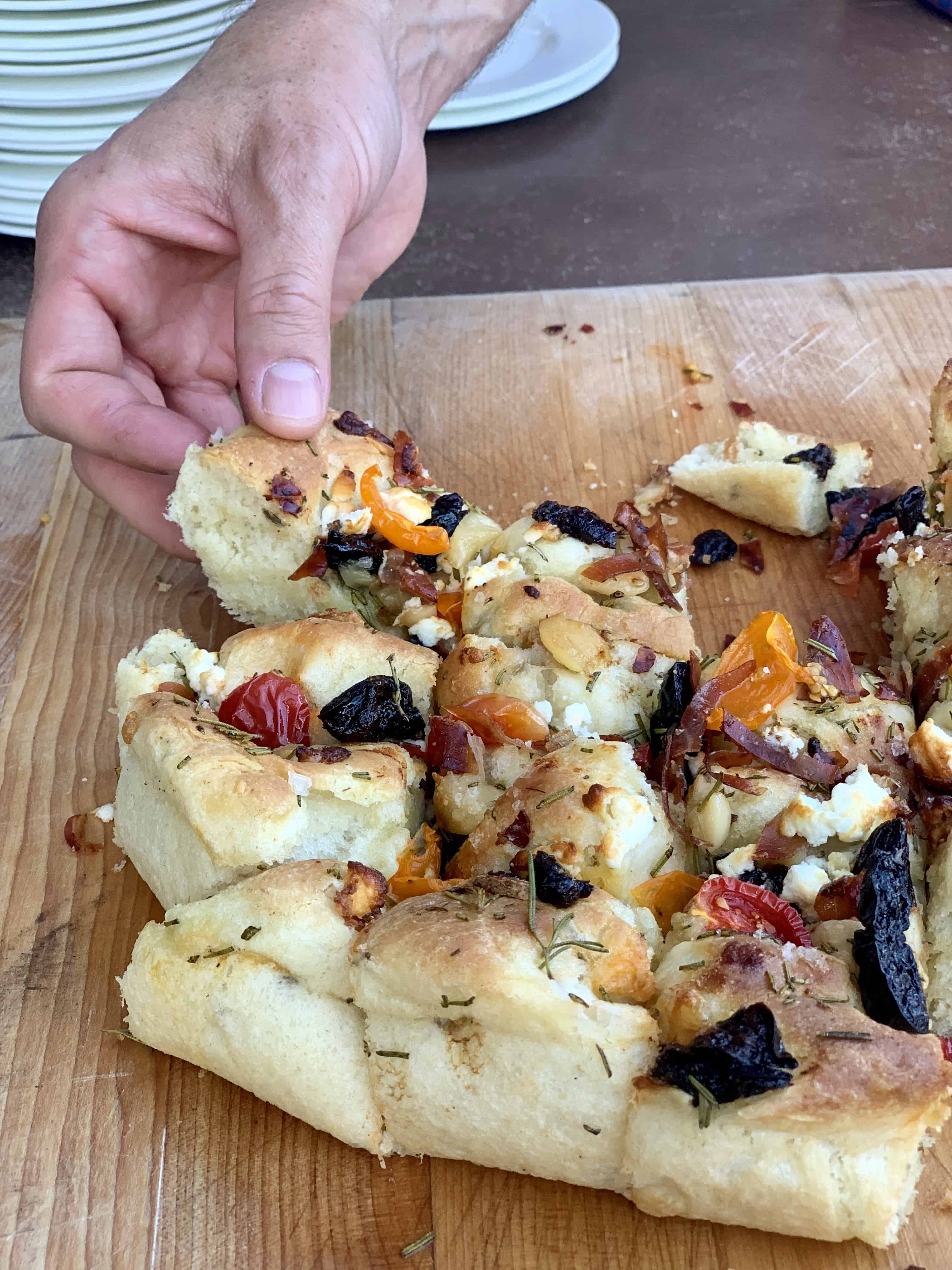 Cast Iron Foccacia Bread with prunes on a cutting board with a cheese pull