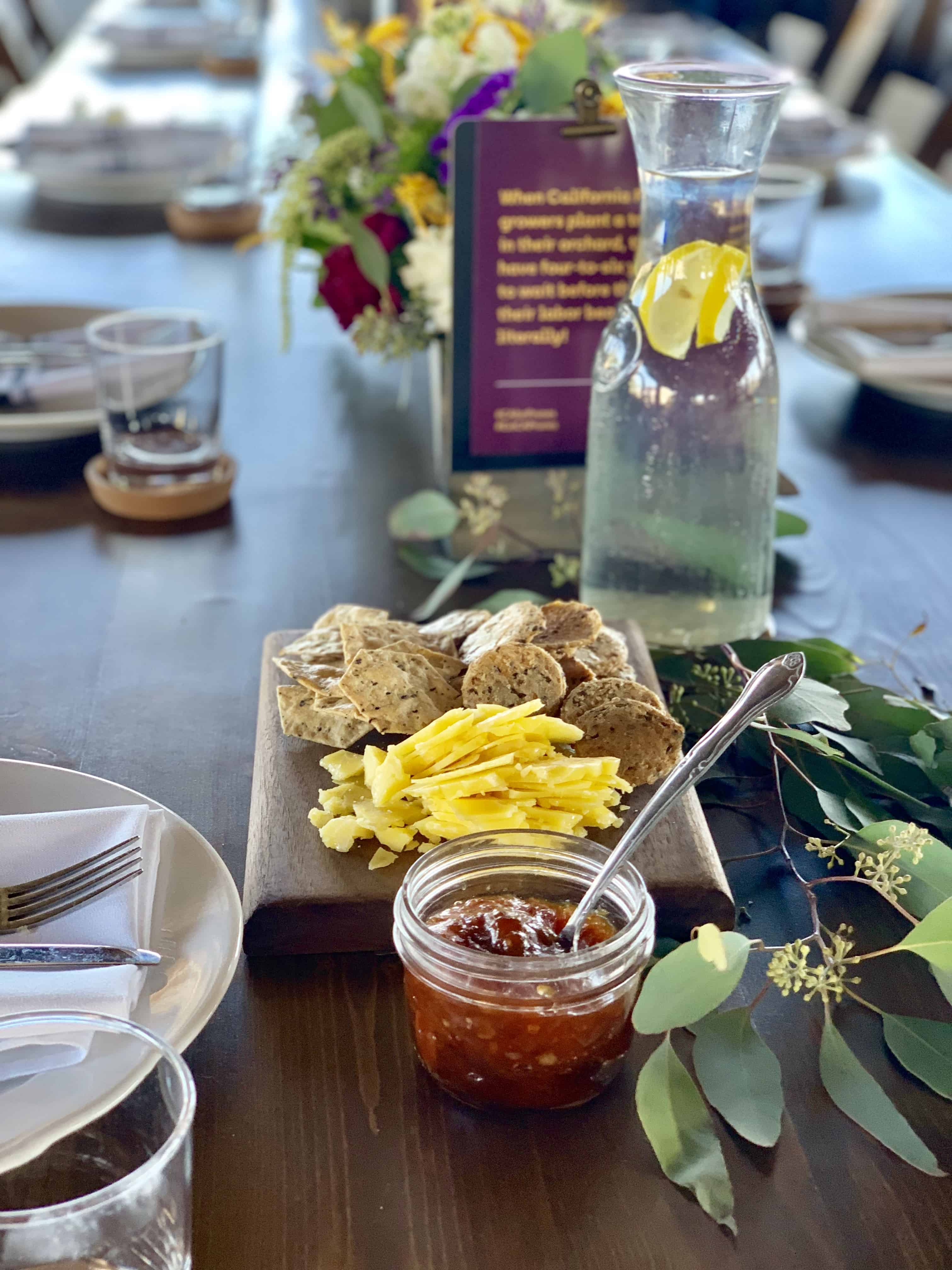 Beautiful tablescape with flowers in the background and cheese, crackers and jam in the foreground.