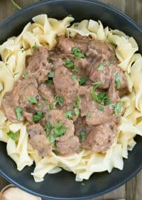 Black plate filled with egg noodles and topped with beef stroganoff. Square overhead picture.