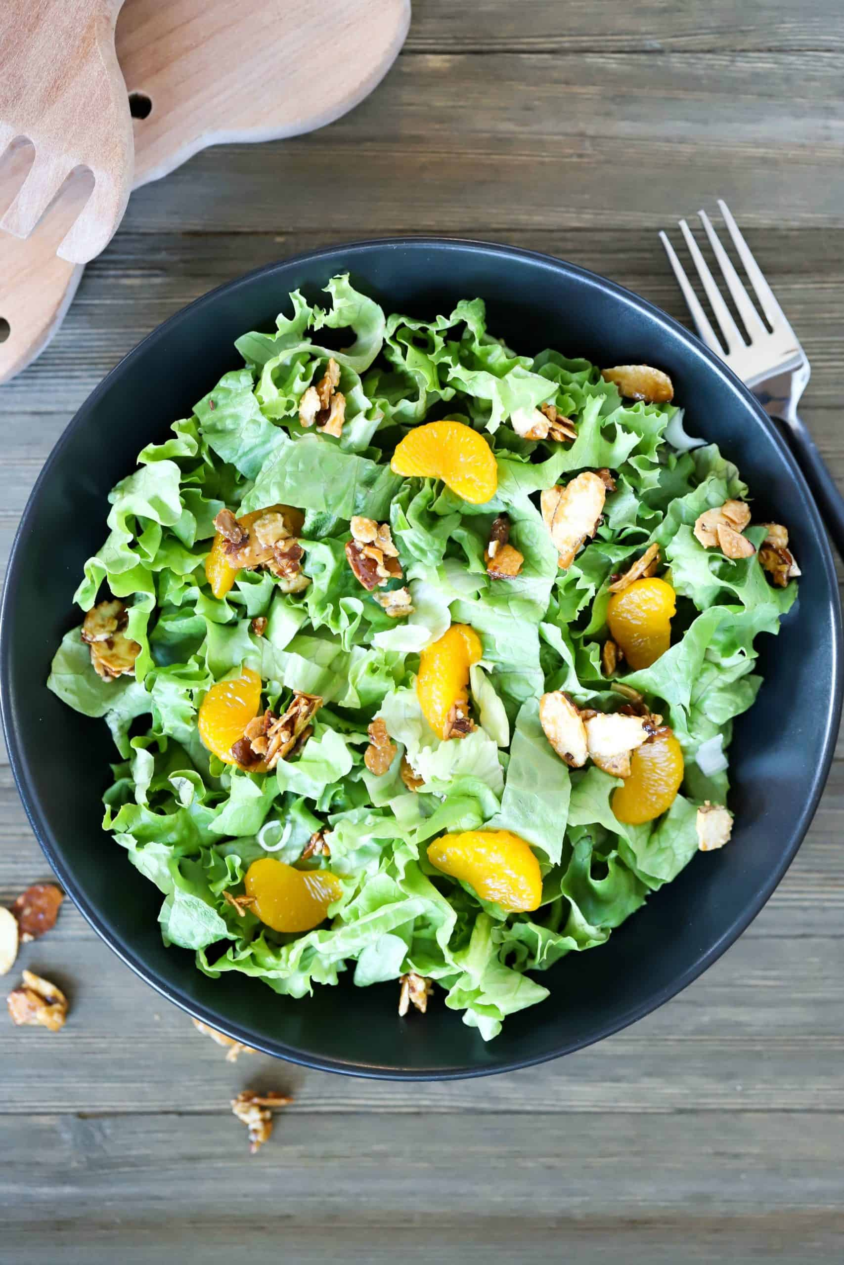 Overhead view of a black plate filled with lettuce, mandarin oranges and toasted almonds.