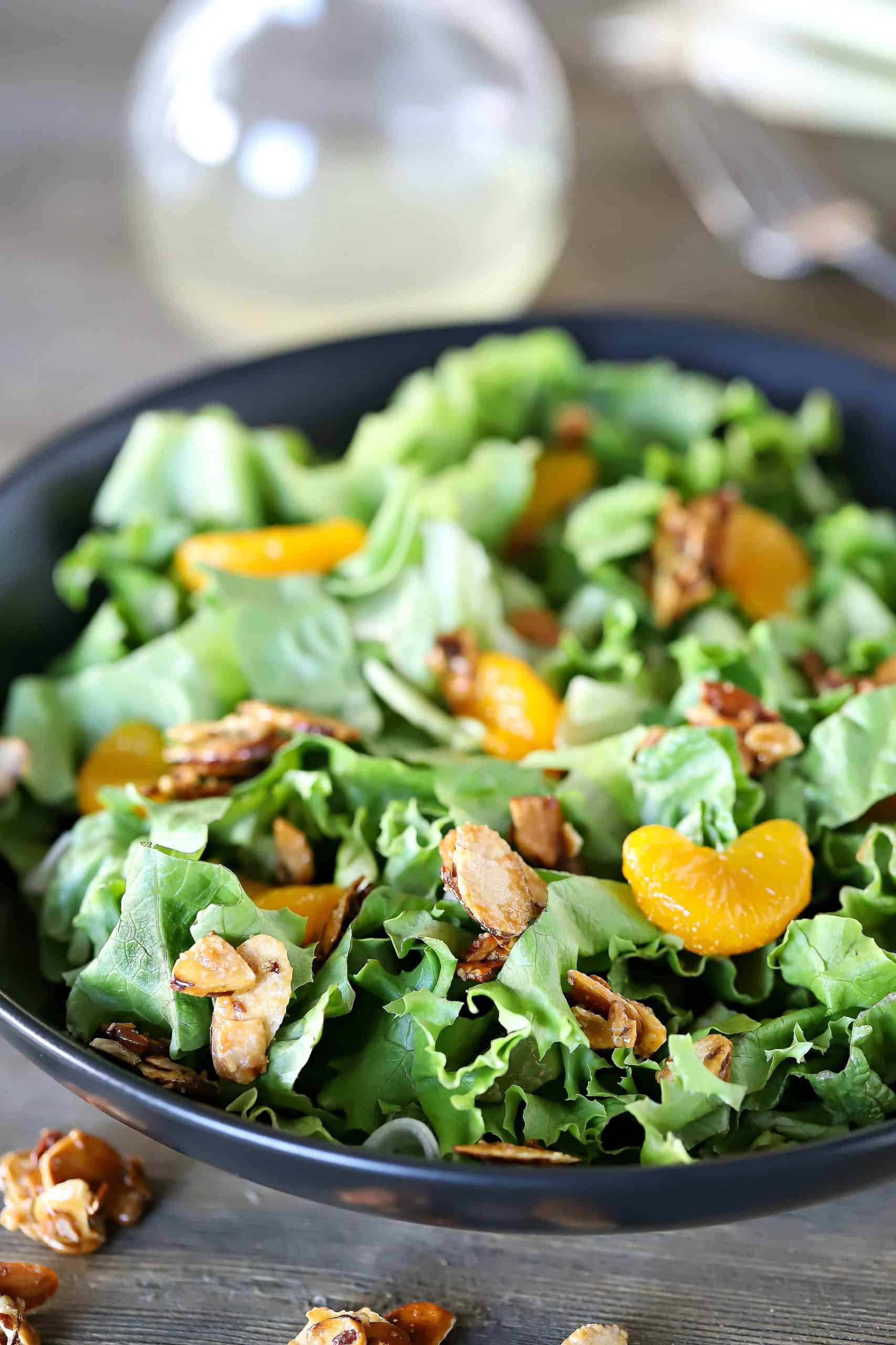 Bowl filled with lettuce mix, and topped with mandarin oranges and toasted almonds.