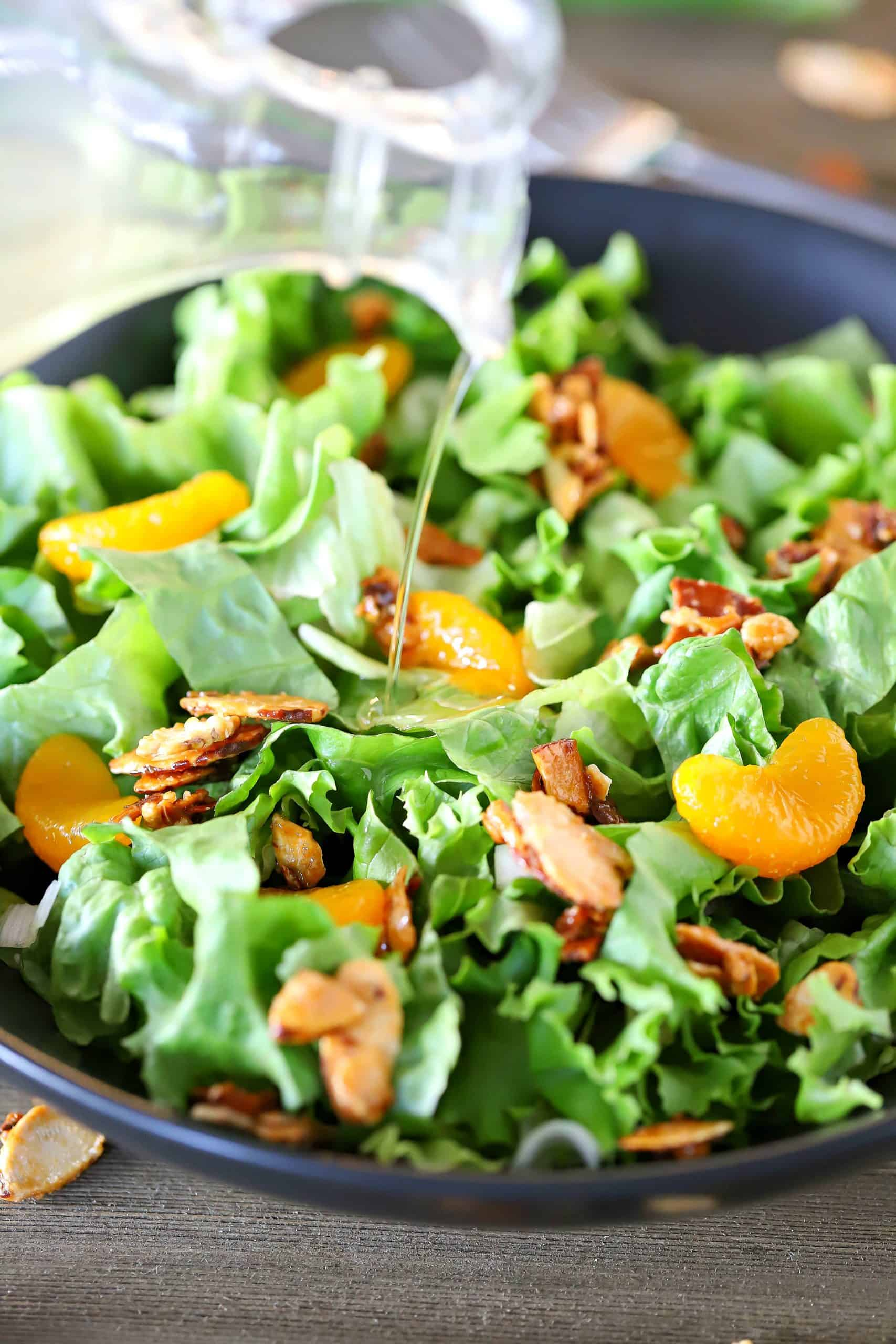 Dressing being poured over a bowl of lettuce, mandarin oranges and toasted almonds.