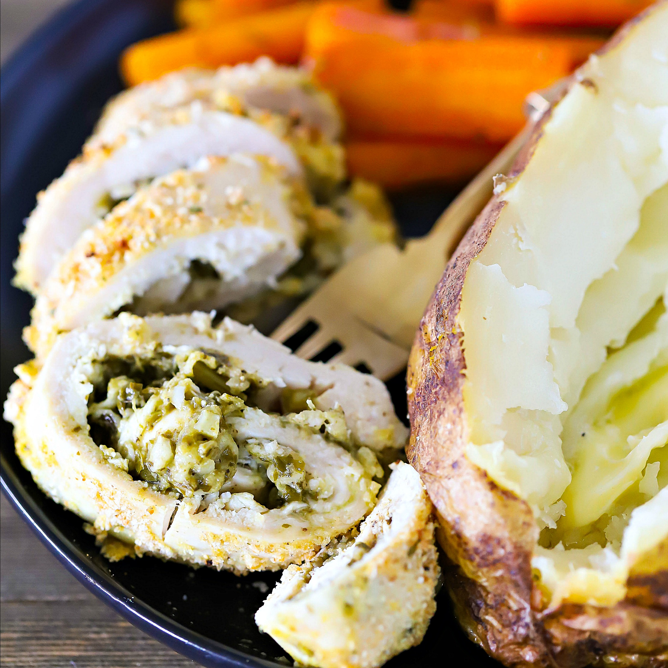 Sliced Pesto Stuffed Chicken on a black plate with a side of carrots and baked potato and a fork.