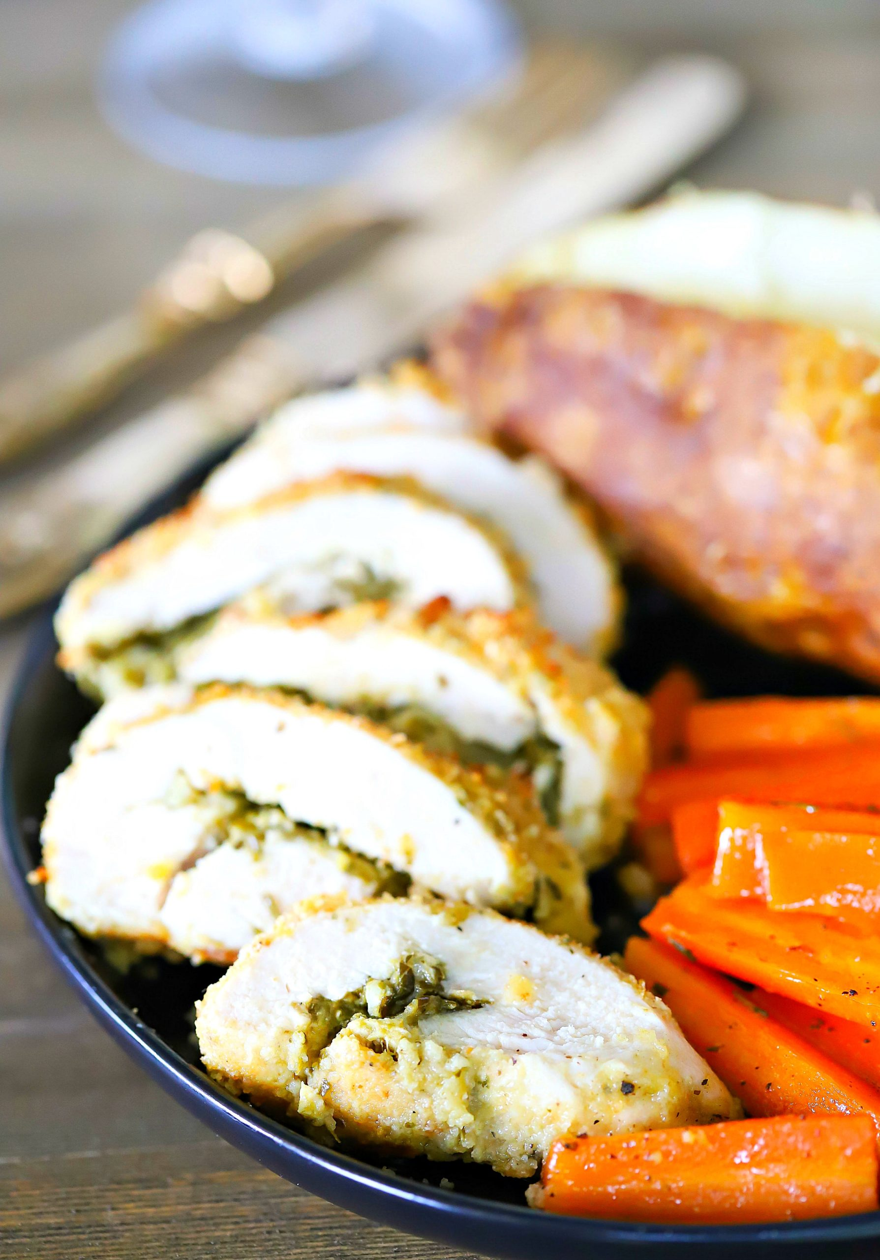 Sliced Pesto Stuffed Chicken on a black plate with a side of carrots