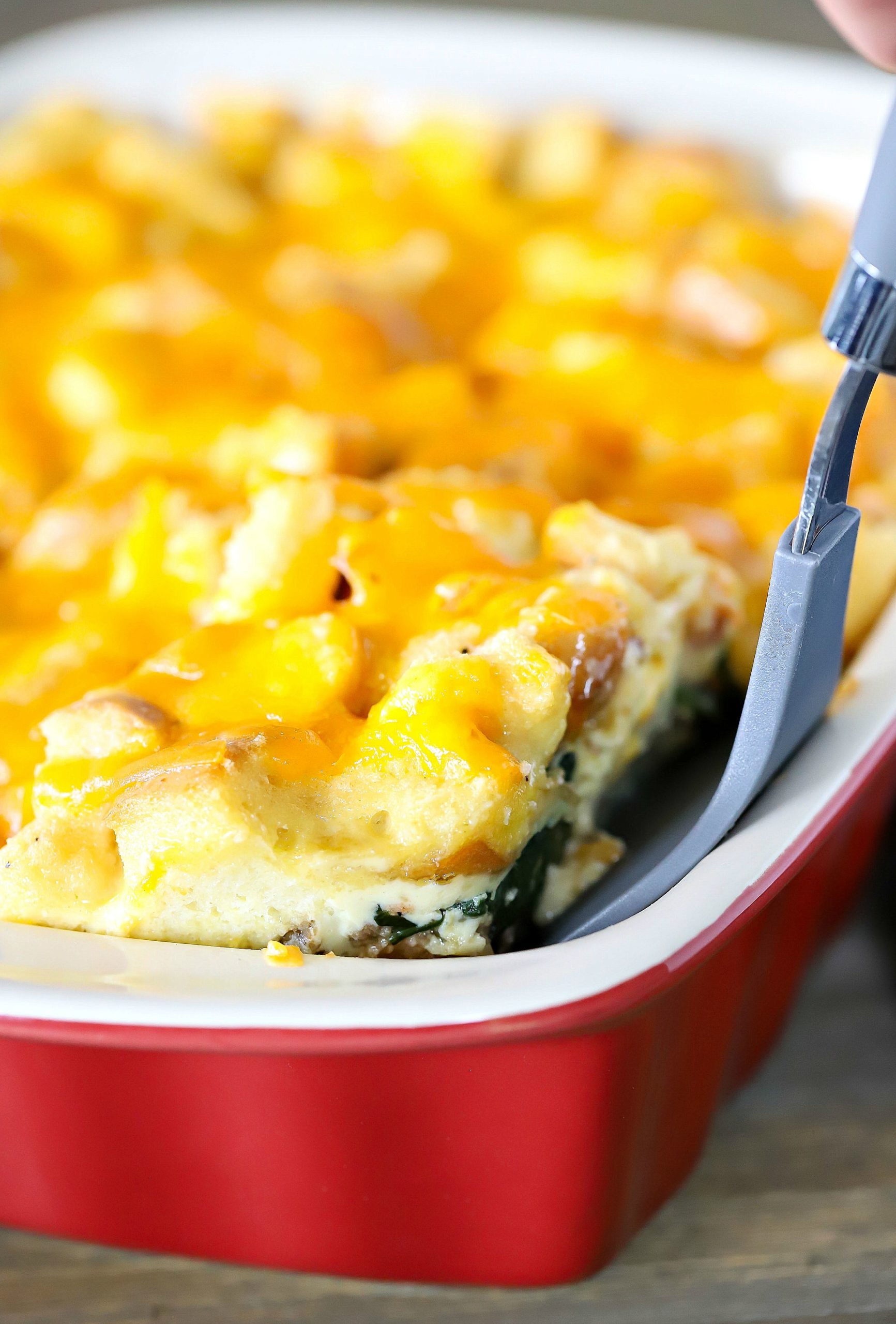 spatula scooping a slice of egg strata from a casserole dish