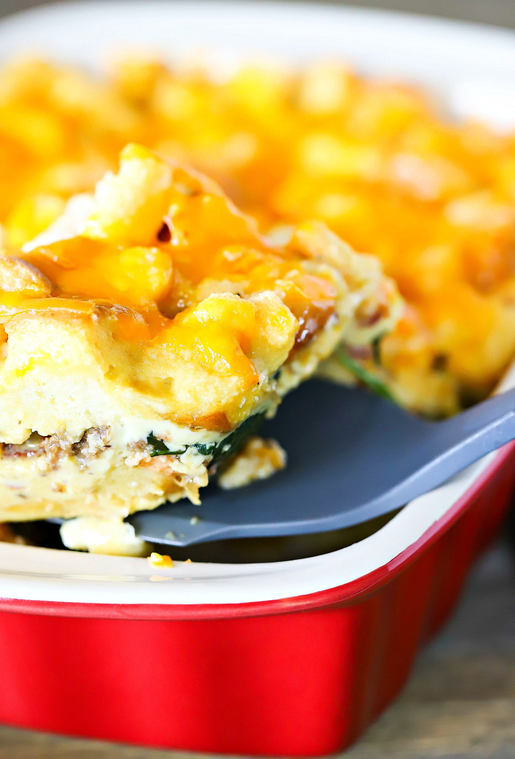 yummy slice of cheesy strata scooped from a casserole dish