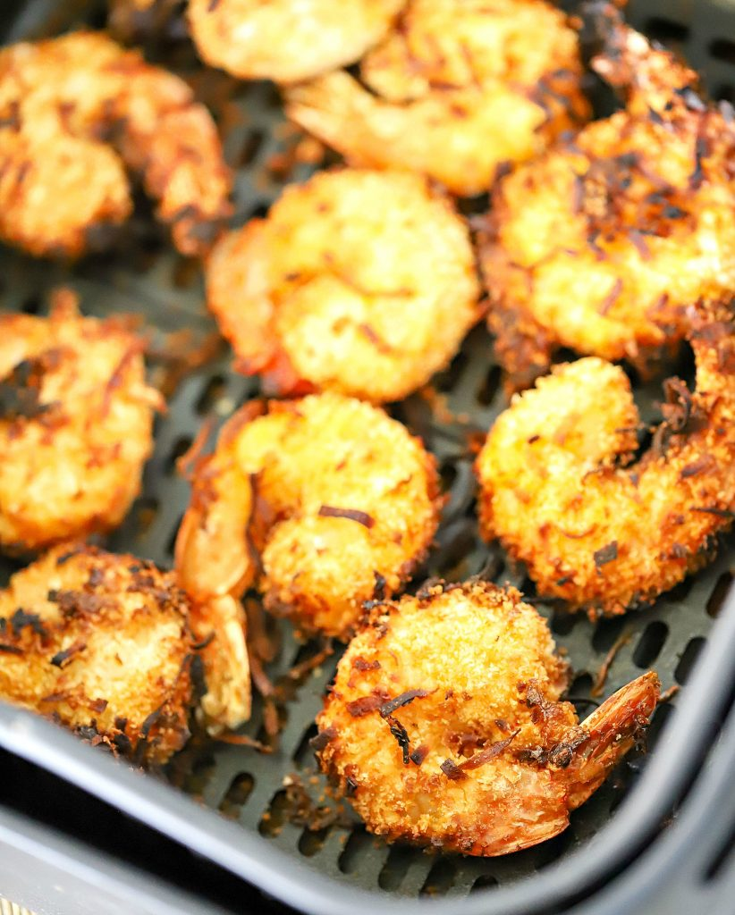 Air fryer basket with 10 cooked coconut shrimp inside