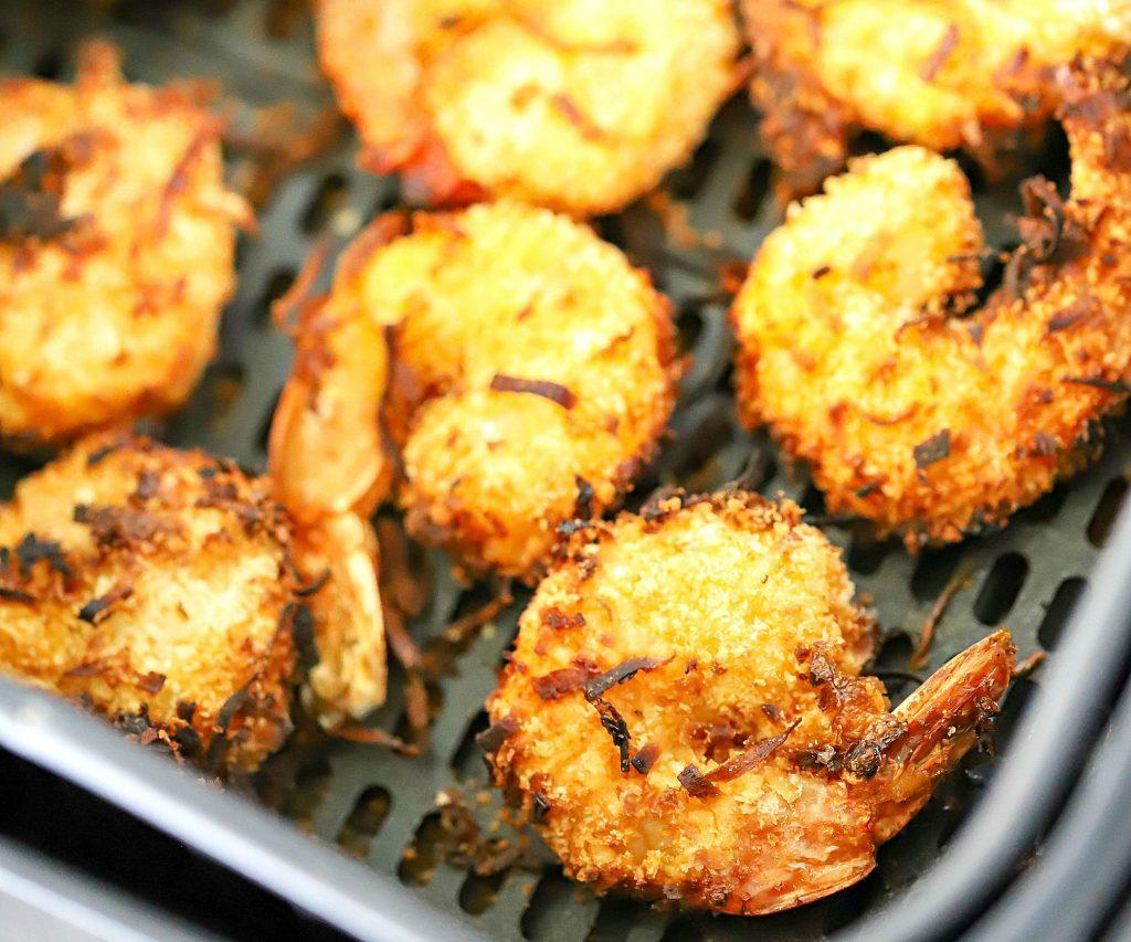 Cesta de fritadeira com camarão de coco cozido dentro