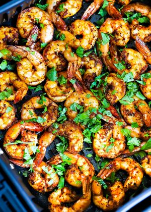 A pile of air fryer shrimp on a white plate.