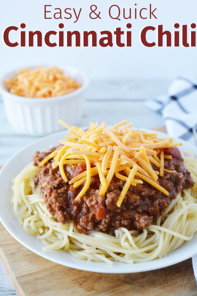 Plate with spaghetti noodles topped with chili and shredded cheese.