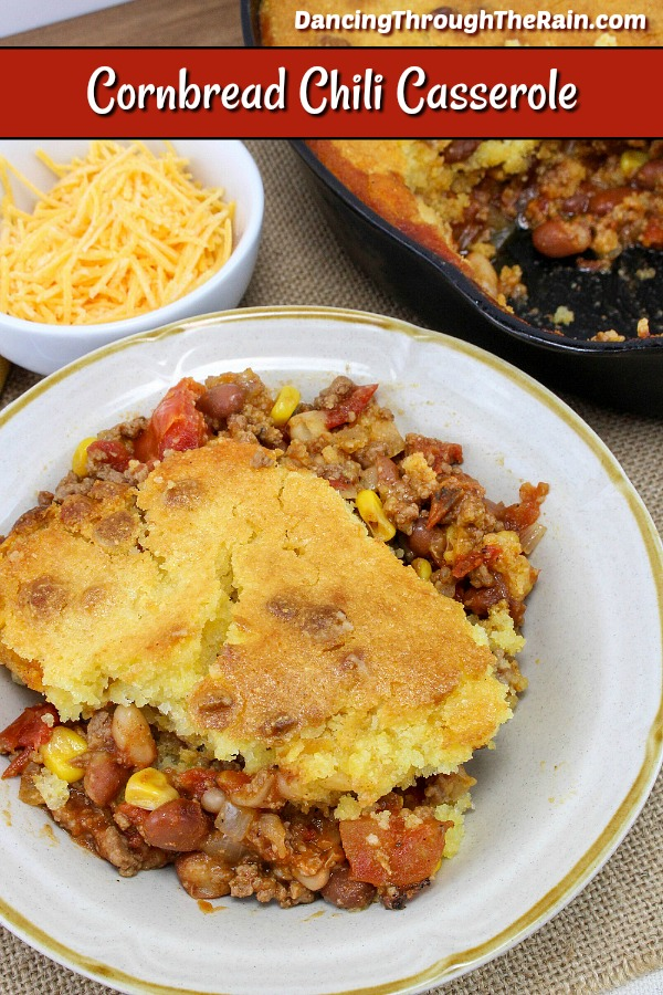 White plate with chili topped with cooked cornbread.