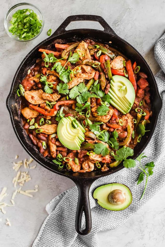 Cast iron photo of a chili recipe with avocado and cilantro toppings.