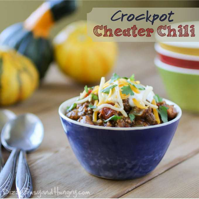 Blue bowl filled with chili and topped with cheese and cilantro.