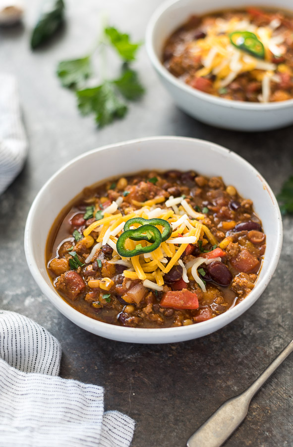 Two bowls of pumpkin chili topped with cheese and jalapeños.